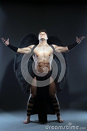 Young muscular man posing as fallen angel