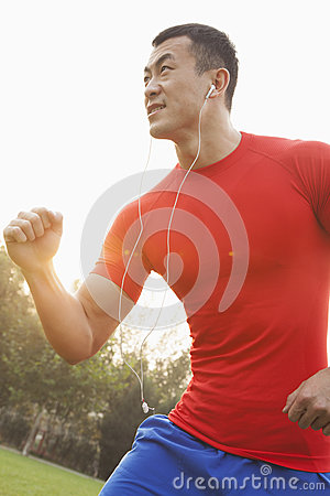 Young muscular man with a red shirt running and listening to music on ear buds outdoors in the park in Beijing, China, with lens f
