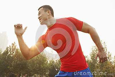 Young muscular man with a red shirt running and listening to music on earbuds outdoors in the park in Beijing, China