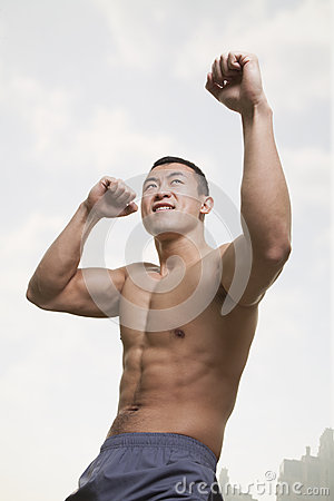 Young, muscular man shadow boxing with arms raised, outdoors in Beijing China