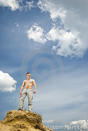 Young muscular man stands in a desert