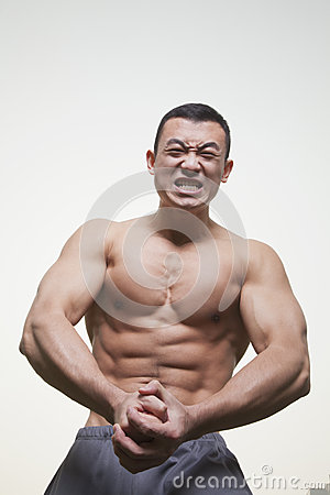 Young, muscular, shirtless man growling and flexing his muscles, studio shot