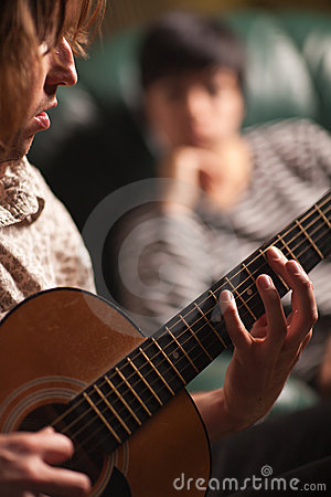 Young Musician Plays His Guitar as Friend Listens