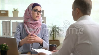 Young muslim business woman shake hands with a caucasian man during a meeting in office. Young professional muslim business woman shake hands with a caucasian stock footage