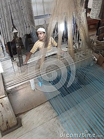 Young muslim man runs a loom to weave silk brocade Editorial Image