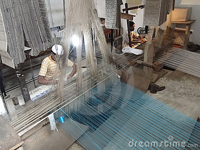 Young muslim man runs a loom to weave silk brocade Editorial Stock Image