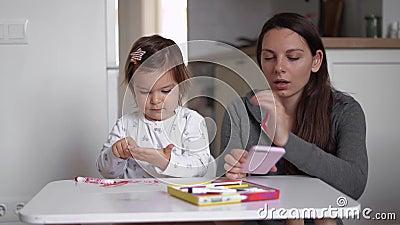 YOung-Mutter, die von zu Hause aus telefoniert und Kleinkinder in der Nähe von Mama spielt Heimbüro, Quarantäne Covid-19 stock video