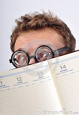 Young nerd hiding behind agenda