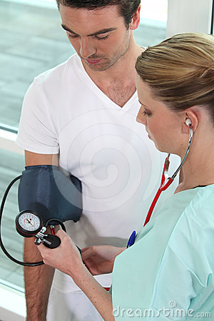 Young nurse taking blood pressure