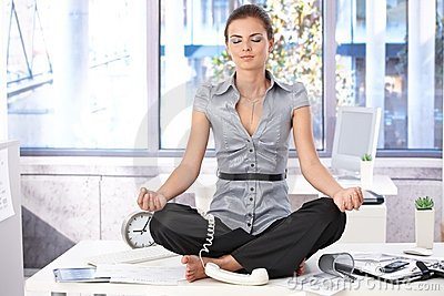 Young office worker meditating on top of desk