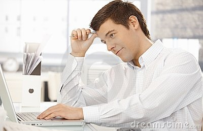 Young office worker thinking in office with laptop