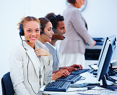 Young operators sitting in office with headsets