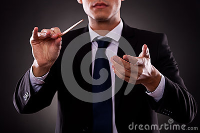 Young orchestra conductor directing with his baton