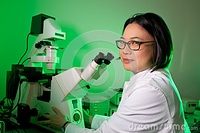 Young oriental scientist with microscope
