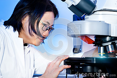 Young oriental scientist tunes her microscope