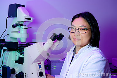 Young oriental scientist works on microscope