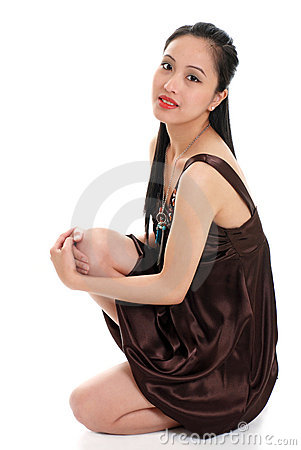Young oriental woman in a brown dress sitting down