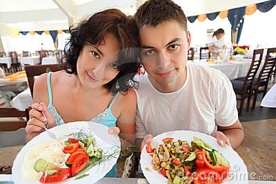 Young pair in cafe with plates with salad