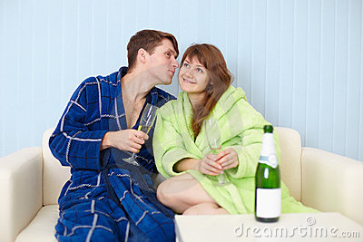 Young pair at home on divan with sparkling wine