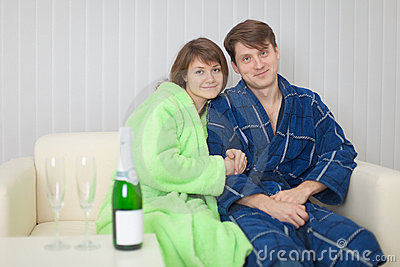 Young pair on a sofa with sparkling wine