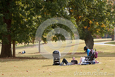 Young Parents Relax On Blanket In Park Editorial Photo