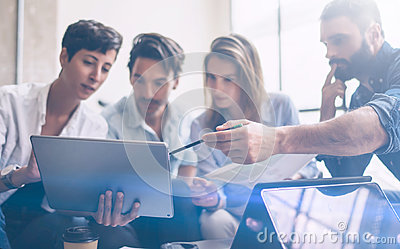 Young partners making research for new business direction. Young businessman working modern laptop and showing documents Stock Photo