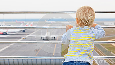 Young Passenger Looks At The Plane In Airport Stock Photo