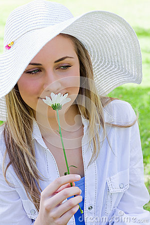 Young peaceful blonde woman smelling a white flower