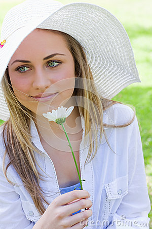 Young peaceful girl holding a white flower in a park