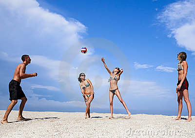 Young people on the beach playing volleyball