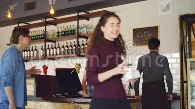 Young people are buying coffee-to-go in nice local cafe and paying with smartphone while friendly workers are greeting. Customers, talking and selling drinks stock footage