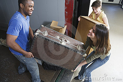 Young people carrying heavy box on moving day.