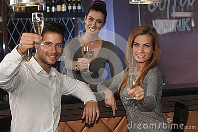 Young people celebrating with champagne in bar