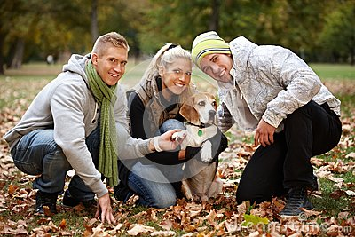 Young people with cute dog in park smiling