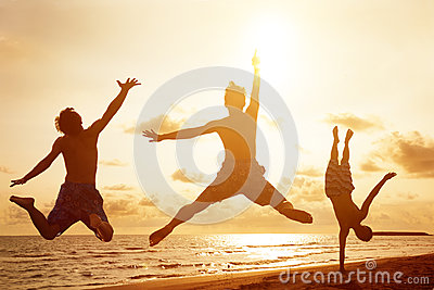 Young people jumping on the beach with sunset