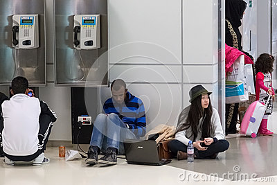 Young people sitting on the floor and waiting for their flight at Doha International Airport Editorial Stock Photo