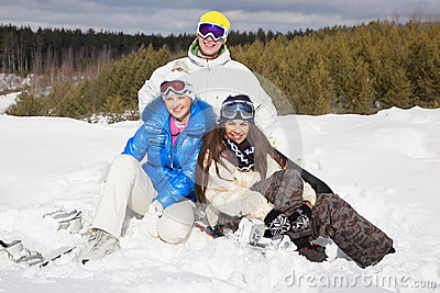 Young people sitting on the snow and smiling