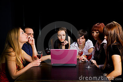 Young people using laptop in a night bar