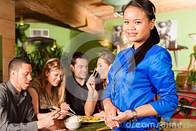 Young people with waitress in Thai restaurant