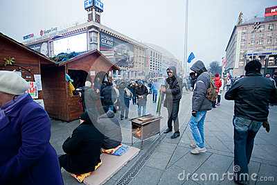 Young people warm themselves by the vintage stove on the street during the week of pro-European protest Editorial Stock Image