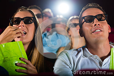 Young people watching 3d movie at cinema