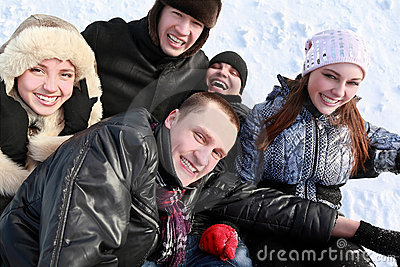 Young people by winter day lie on snow