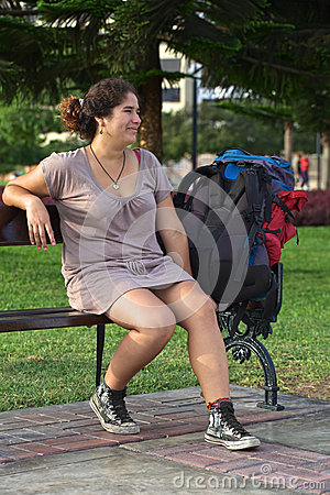 Young Peruvian Woman on Bench with Backpack
