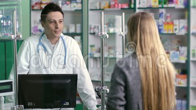 Young pharmacist counseling customer in pharmacy stock footage