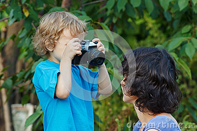 Young photographer with a camera shoots her mother