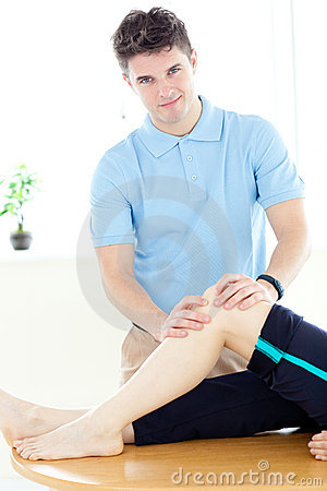Young physical therapist giving a leg massage