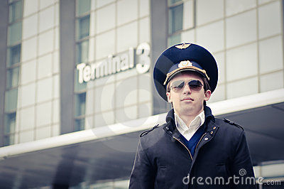 Young pilot in Kastrup airport against terminal th