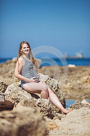 Young pregnant woman breathes the fresh sea air on a background of mountains