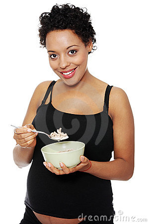 Young pregnant woman eating muesli
