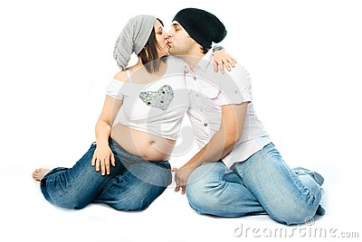 Young pregnant woman and her husband kissing